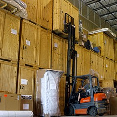 forklift lifting crate in warehouse